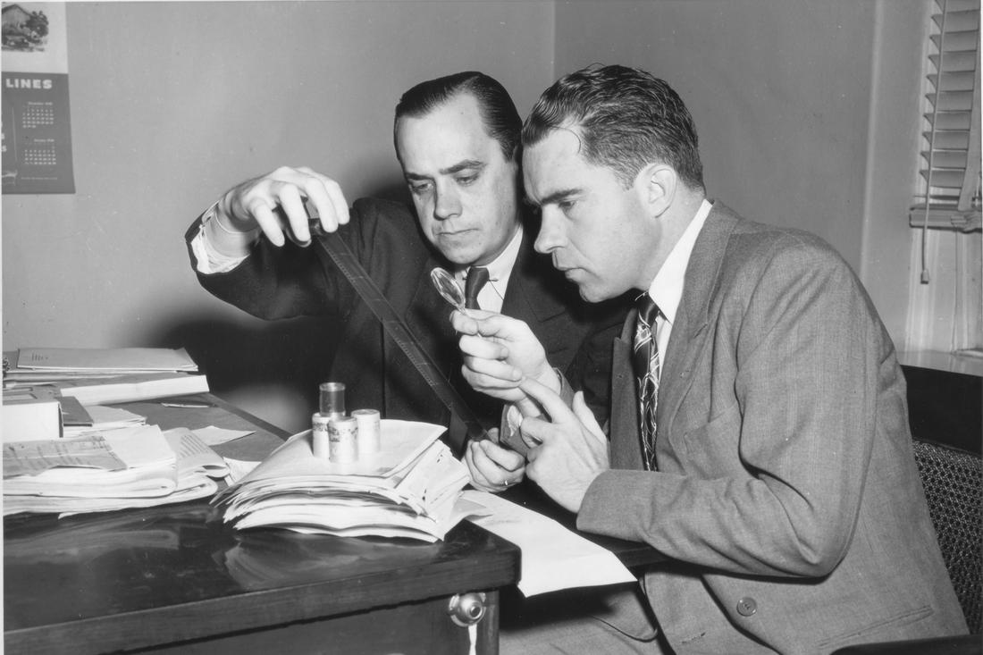 Photo: RN studies microfilm with HUAC Special Investigator Robert Stripling.