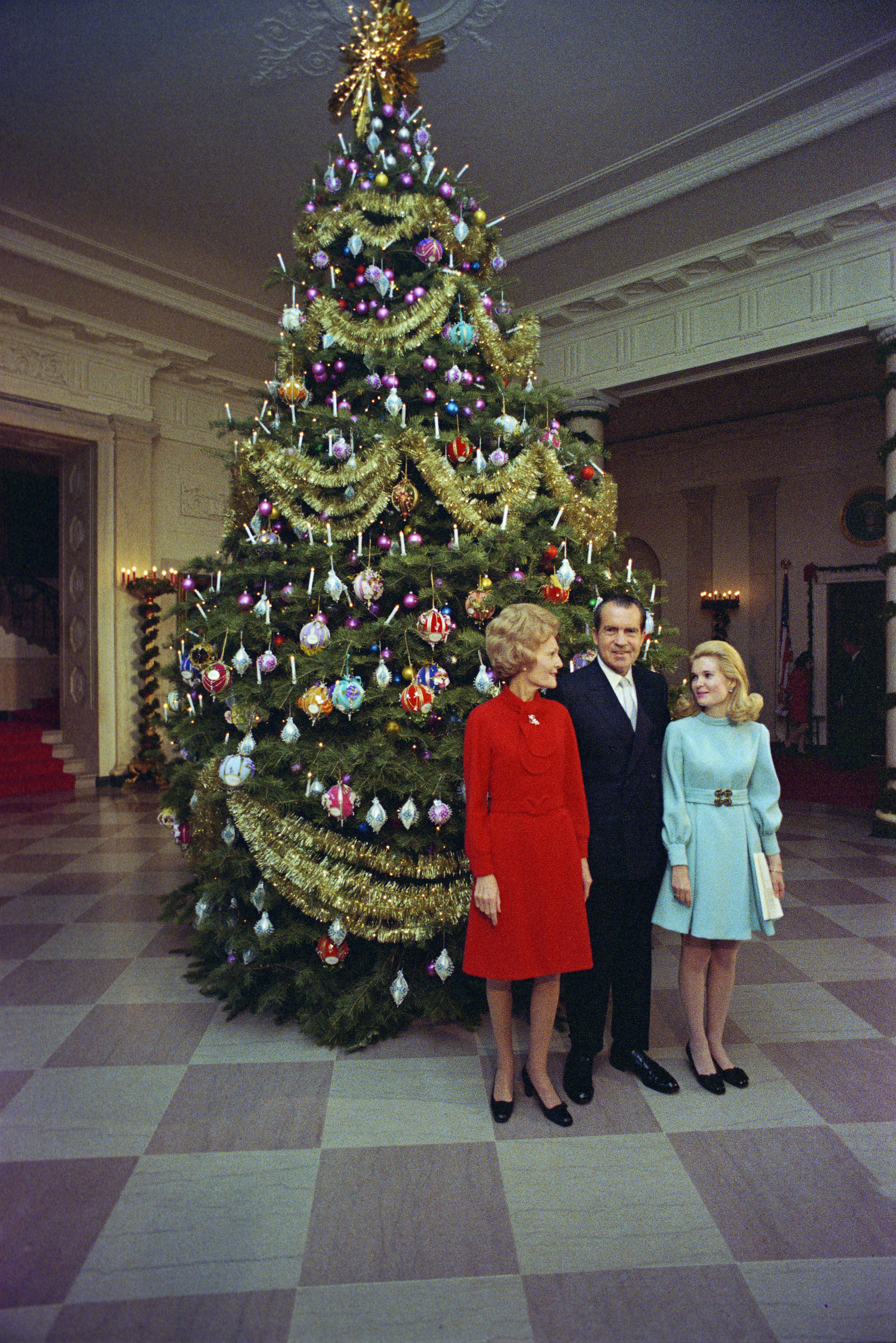 C2675-11: President and Mrs. Nixon pose in front of the White House Christmas Tree with daughter Tricia