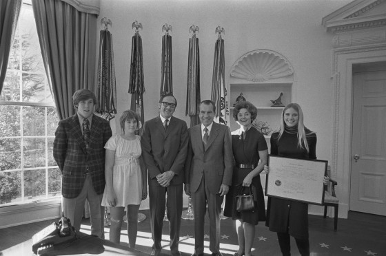 President Nixon poses with newly confirmed Supreme Court Justice William Rehnquist and his family, as his daughter displays his certificate of commission to the Court